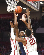 West Virginia guard Oscar Tshiebwe, center, goes up for a shot against Oklahoma forwards Kristian Doolittle (21) and Kur Kuath, left, during the first half of an NCAA college basketball game in Norman, Okla., Saturday, Feb. 8, 2020. (AP Photo/Kyle Phillips)