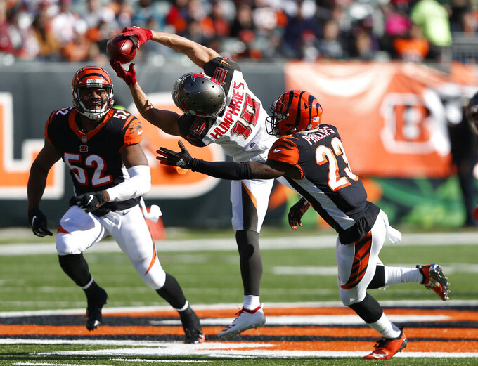 "FILE - In this Oct. 28, 2018,. file photo, Tampa Bay Buccaneers wide receiver Adam Humphries (10) makes a catch between Cincinnati Bengals cornerback Darius Phillips (23) and linebacker Preston Brown (52) during the second half of an NFL football game, in Cincinnati. For Adam Humphries, Tennessee has been a potential destination for months based on his relationship with Titans general manager Jon Robinson because of their Tampa Bay connection. Not even a late push by the New England Patriots could sway him to walk away from his deal with the Titans. Even considering how much success wide receivers like Humphries have enjoyed with the defending Super Bowl champs.""Obviously, I'm a man of my word, and I'm going to keep my word there,"" Humphries said Thursday, March 14, 2019, after signing with Tennessee. (AP Photo/Frank Victores, File)"