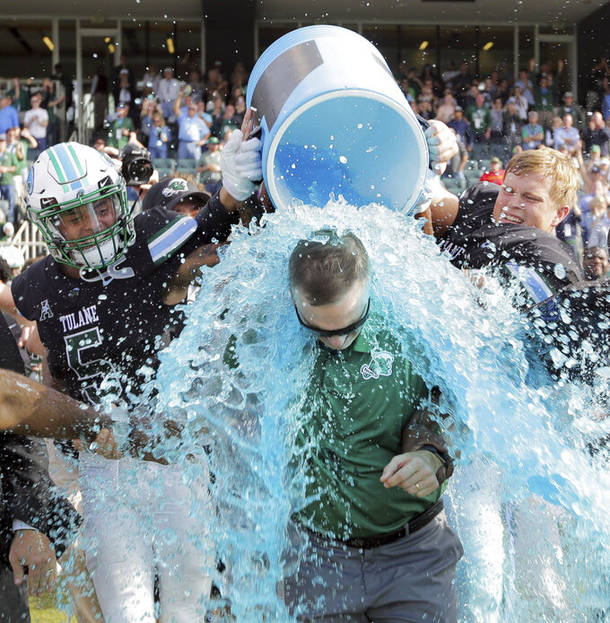 Tulane head coach Willie Fritz gets doused after beating the Navy 29-28 in an NCAA college football game at Yulman Stadium in New Orleans, Saturday, Nov. 24, 2018. (David Grunfeld/The Times-Picayune via AP)