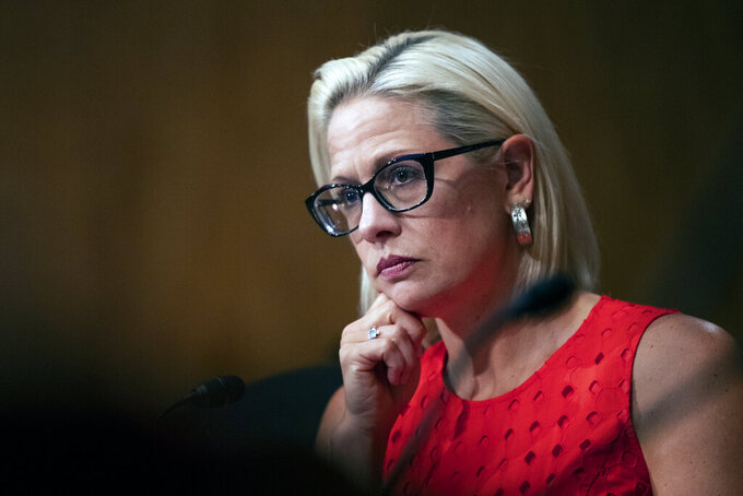 FILE - In this July 16, 2019, file photo, Senate Security and Governmental Affairs Committee member Sen. Kyrsten Sinema, D-Ariz., listens to witnesses during a hearing on 2020 census on Capitol Hill in Washington. More than her shock of purple hair or unpredictable votes Sinema is perhaps best known for doing the unthinkable in Washington: spending time on the Republican side of the aisle. Her years in Congress have been a whirlwind of political style and perplexing substance, an anti-war liberal-turned-deal-making centrist who now finds herself at the highest levels of power. (AP Photo/Manuel Balce Ceneta)