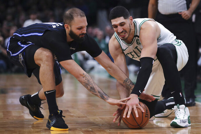 Boston Celtics center Enes Kanter, right, and Orlando Magic guard Evan Fournier, left, reach for the ball during the fourth quarter of an NBA basketball game in Boston, Wednesday, Feb. 5, 2020. (AP Photo/Charles Krupa)