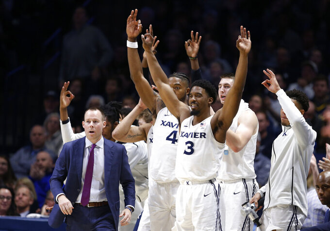 The Xavier bench, including head coach Travis Steele, left, cheer a 3-point basket against St. John's during the second half of an NCAA college basketball game, Sunday, Jan. 5, 2020, in Cincinnati. Xavier won 75-67. (AP Photo/Gary Landers)