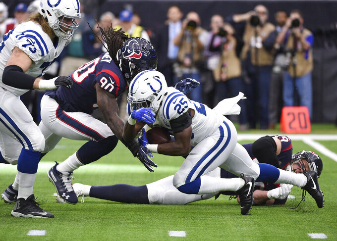 Indianapolis Colts running back Marlon Mack (25) is hit by Houston Texans outside linebacker Jadeveon Clowney (90) on a run during the first half of an NFL wild card playoff football game, Saturday, Jan. 5, 2019, in Houston. (AP Photo/Eric Christian Smith)