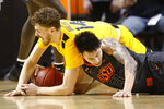 West Virginia guard Chase Harler (14) and Oklahoma State guard Lindy Waters III (21) reach for the ball in the second half of an NCAA college basketball game in Stillwater, Okla., Monday, Jan. 6, 2020. (AP Photo/Sue Ogrocki)