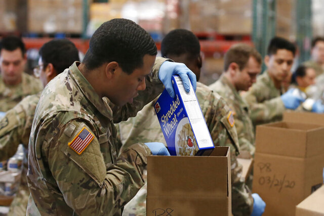 Grant Mock, a PFC with the California National Guard places cereal in a box of food supplies at the Sacramento Food Bank in Sacramento, Calif., Saturday, March 21, 2020. Food banks have been hit hard by a shortage of volunteers due to the mandatory stay-at-home order caused by the coronavirus. Mock and other members of the 115th Regional Support Group are supplementing food bank staff to ensure the food bank continues provide food to those in need. (AP Photo/Rich Pedroncelli)