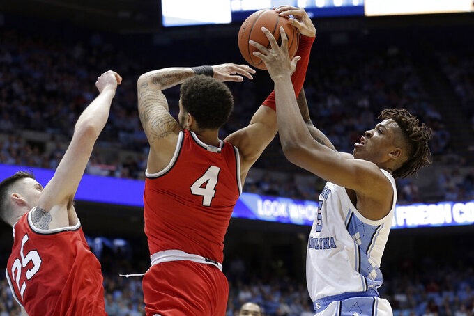 Ohio State guard Duane Washington Jr., center, and forward Kyle Young, left, struggle for possession of the ball with North Carolina forward Armando Bacot, right, during the first half of an NCAA college basketball game in Chapel Hill, N.C., Wednesday, Dec. 4, 2019. (AP Photo/Gerry Broome)
