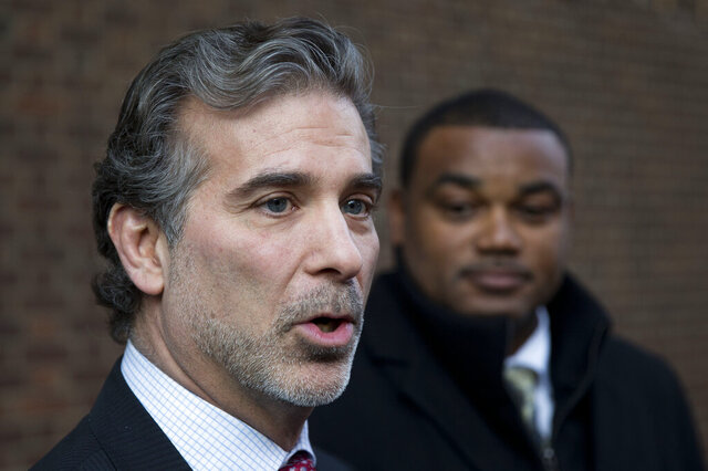 FILE - In this Nov. 19, 2014, file photo, co-lead players' lawyer Christopher Seeger, left, and client former NFL player Shawn Wooden speak with members of the media after a hearing on the proposed NFL concussion settlement outside of the U.S. Courthouse in Philadelphia. After several years of infighting over $112 million in legal fees in the NFL concussion case, a federal appeals court has approved a plan to give nearly half the money to Seeger's firm. The decision Thursday, May 7, 2020, grants New York-based Seeger Weiss over $51 million, more than 10 times the amount of any other firm, including the lawyers who filed the first cases in 2012. (AP Photo/Matt Rourke, File)
