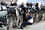 Riot policemen detain a pro-democracy protester during a rally in Hong Kong, Sunday, Dec. 1, 2019. A huge crowd took to the streets of Hong Kong on Sunday, some driven back by tear gas, to demand more democracy and an investigation into the use of force to crack down on the six-month-long anti-government demonstrations. (AP Photo/Vincent Thian)
