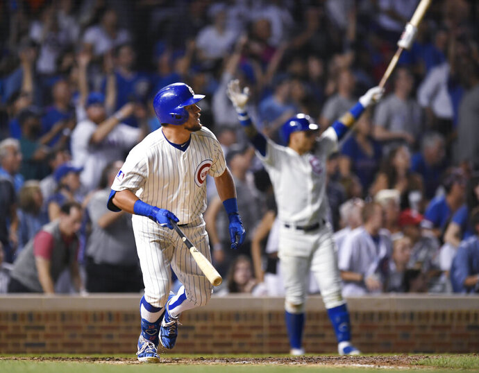 Chicago Cubs' Kyle Schwarber watches his game-ending solo home run while teammate Javier Baez back, celebrates during the 10th inning of a baseball game against the Cincinnati Reds on Tuesday, July 16, 2019, in Chicago. (AP Photo/Paul Beaty)