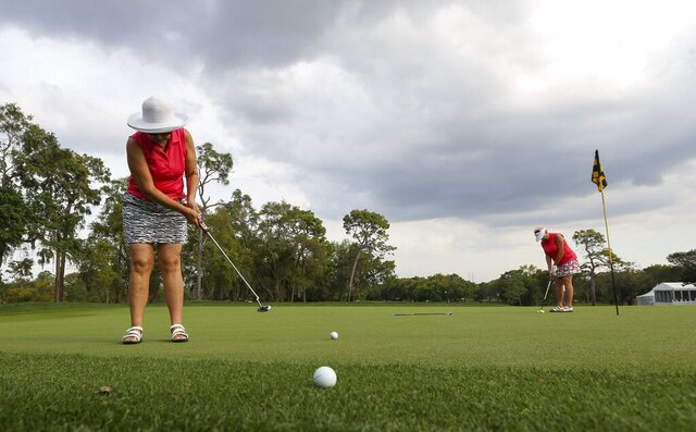 Florine Mason, 69, left, putts as her friend Elaine Sterner, 76, lines up a putt as they practice along the Copperhead course at Innisbrook Golf Resort, Monday, March 16, 2020, in Palm Harbor, Fla. With the Valspar Tournament shut down due to the coronavirus outbreak, golfers had the unique opportunity to play on a tour-ready golf course. (Chris Urso/Tampa Bay Times via AP)