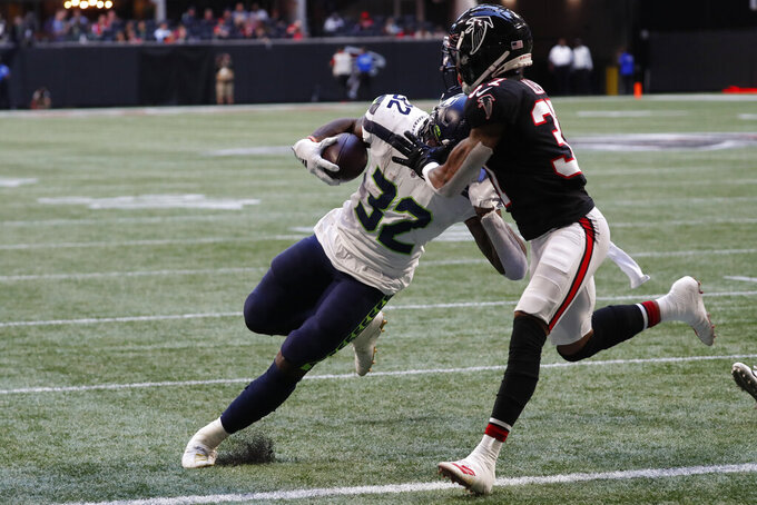 Seattle Seahawks running back Chris Carson (32) runs into the end zone against Atlanta Falcons free safety Ricardo Allen (37) during the first half of an NFL football game, Sunday, Oct. 27, 2019, in Atlanta. (AP Photo/John Bazemore)