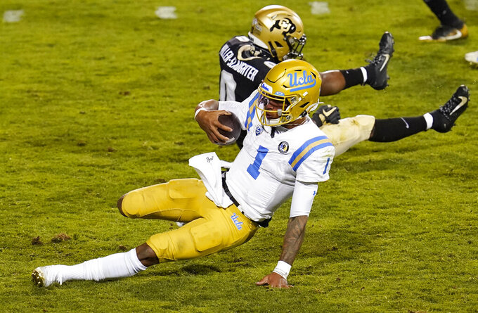 UCLA quarterback Dorian Thompson-Robinson, front, slides to a stop past Colorado cornerback Chris Miller after a long gain in the second half of an NCAA college football game Saturday, Nov. 7, 2020, in Boulder, Colo. (AP Photo/David Zalubowski)