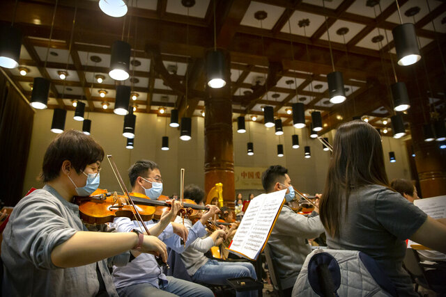 Musicians from the Wuhan Philharmonic Orchestra rehearse a day before their concert to open the Beijing Music Festival, China's first classical music festival since the beginning of the COVID-19 outbreak, in Beijing, Friday, Oct. 9, 2020. China is holding its first classical music festival since the outbreak of the coronavirus pandemic featuring musicians from the global epicenter of Wuhan, in an attempt to aid in the psychological and emotional healing process. (AP Photo/Mark Schiefelbein)