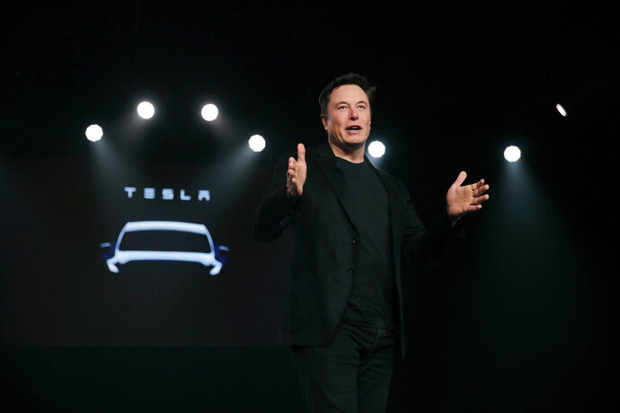 FILE- In this March 14, 2019, file photo Tesla CEO Elon Musk speaks before unveiling the Model Y at Tesla's design studio in Hawthorne, Calif. Shares of electric vehicle maker Tesla Inc. fell at the opening bell Thursday, May 23 but recovered into positive territory after an analyst predicted falling demand but Musk told employees that orders are up. The gyrations within an hour of when the markets opened were indicators of a volatile day for the shares, which have shed about 40 percent of their value this year and are trading at the lowest levels since late 2016.  (AP Photo/Jae C. Hong, File)