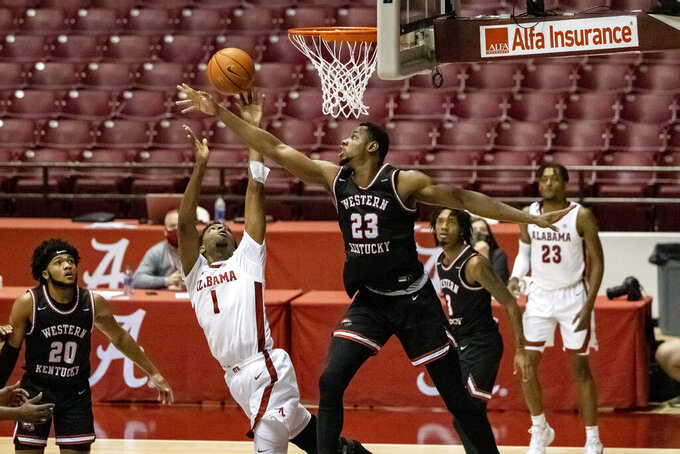 Western Kentucky center Charles Bassey (23) defends Alabama forward/guard Herbert Jones (1) on the final shot of the game, an Alabama miss, that sealed a 73-71 win during the second half of an NCAA college basketball game, Saturday, Dec. 19, 2020, in Tuscaloosa, Ala. (AP Photo/Vasha Hunt)