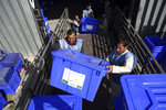 In this Monday, Sept. 23, 2019 photo, Afghan election workers load ballot boxes and other election materials on a truck for distribution at the Independent Election Commission compound, in Kabul, Afghanistan. Millions of Afghans are expected to go to the polls on Saturday to elect a new president, despite an upsurge of violence in the weeks since the collapse of a U.S.-Taliban deal to end America's longest war, and the Taliban warning voters to say away from the polls. (AP Photo/Rahmat Gul)