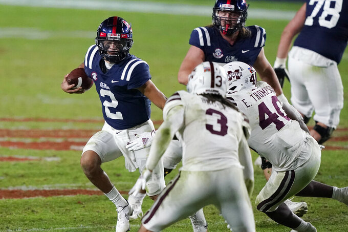 Mississippi quarterback Matt Corral (2) is pursued by Mississippi State defenders as he runs for short yardage during the second half of an NCAA college football game Saturday, Nov. 28, 2020, in Oxford, Miss. Mississippi won 31-24. (AP Photo/Rogelio V. Solis)