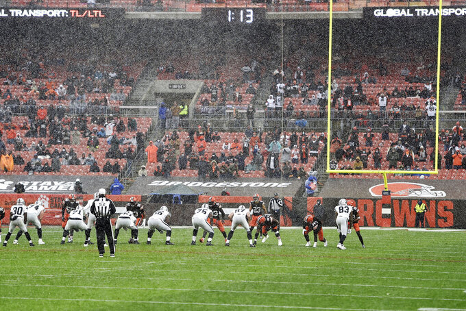 FILE - In this Sunday, Nov. 1, 2020, file photo, the Cleveland Browns and the Las Vegas Raiders line up as snow falls during an NFL football game in Cleveland. Browns center JC Tretter, president of the players' union, has called for all NFL stadiums to put in natural grass fields; this season, 17 stadiums have it, while 13 have synthetic surfaces. (AP Photo/David Richard, File)