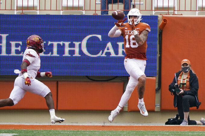 Texas wide receiver Kelvontay Dixon (16) catches a pass for a touchdown past Iowa State defensive back Isheem Young (1) during the second half of an NCAA college football game, Friday, Nov. 27, 2020, in Austin, Texas. (AP Photo/Eric Gay)