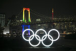 The illuminated Olympic rings float in the water as the Rainbow Bridge and the Tokyo Tower are visible in the distance Friday, Jan. 24, 2020, in the Odaiba district of Tokyo. Tokyo put on a flashy fireworks display on Friday to mark the 6-months-to-go milestone for this summer's Olympics. (AP Photo/Jae C. Hong)