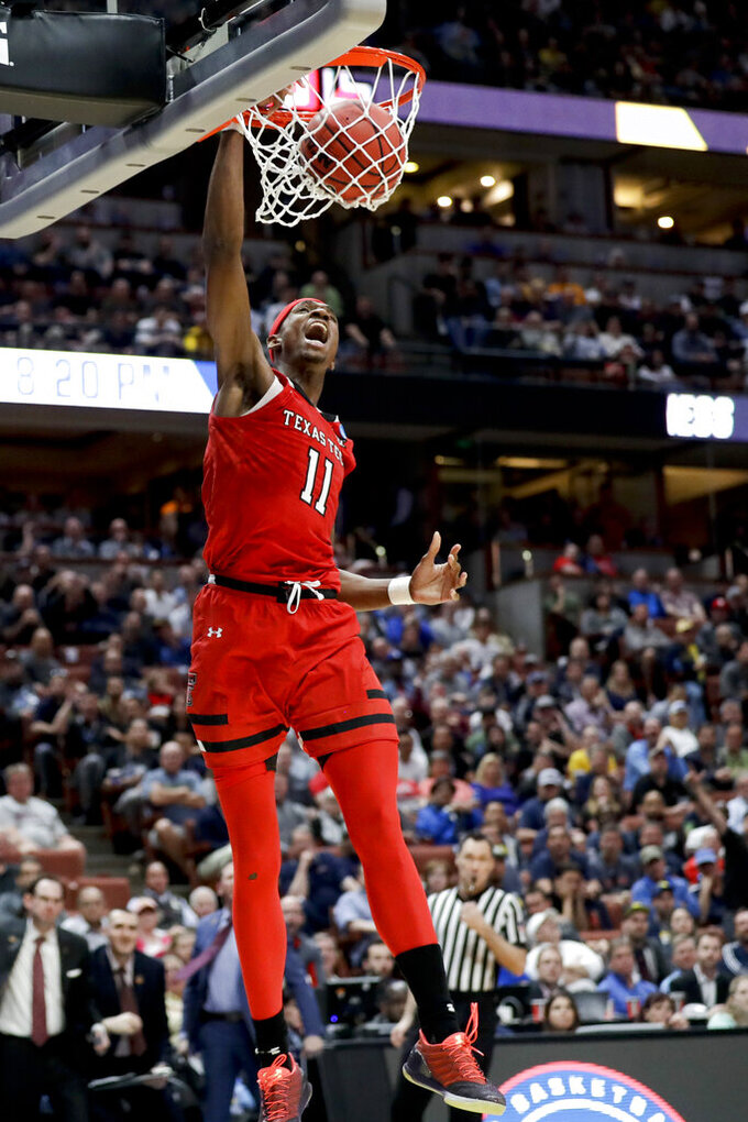 Texas Tech forward Tariq Owens scores against Michigan during the second half an NCAA men's college basketball tournament West Region semifinal Thursday, March 28, 2019, in Anaheim, Calif. (AP Photo/Marcio Jose Sanchez)