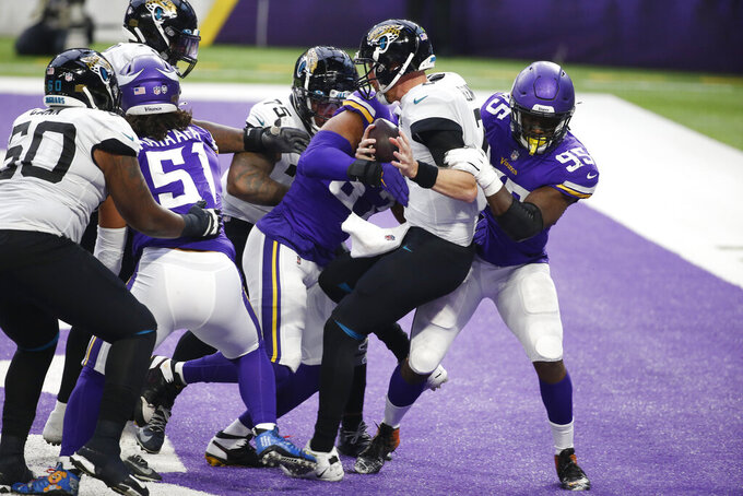 Jacksonville Jaguars quarterback Mike Glennon (center) is tackled for a safety by Minnesota Vikings defensive end Ifeadi Odenigbo, right, during the second half of an NFL football game, Sunday, Dec. 6, 2020, in Minneapolis. (AP Photo/Bruce Kluckhohn)