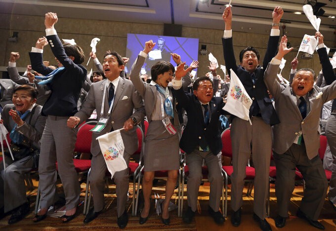 FILE - In this Sept. 7, 2013, file photo, then Japan's Prime Minister Shinzo Abe, second from right, and other members of the Japanese delegation celebrate as then International Olympic Committee (IOC) President Jacques Rogge announces that Tokyo will host the 2020 Olympic Games during the 125th IOC session in Buenos Aires, Argentina. (Ian Watson/Pool Photo via AP, File)