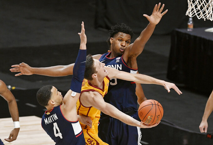 Southern California's Drew Peterson, center, shoots under pressure from Connecticut's Tyrese Martin, left, and  Josh Carlton during the second half of an NCAA college basketball game Thursday, Dec. 3, 2020, in Uncasville, Conn. (AP Photo/Jessica Hill)