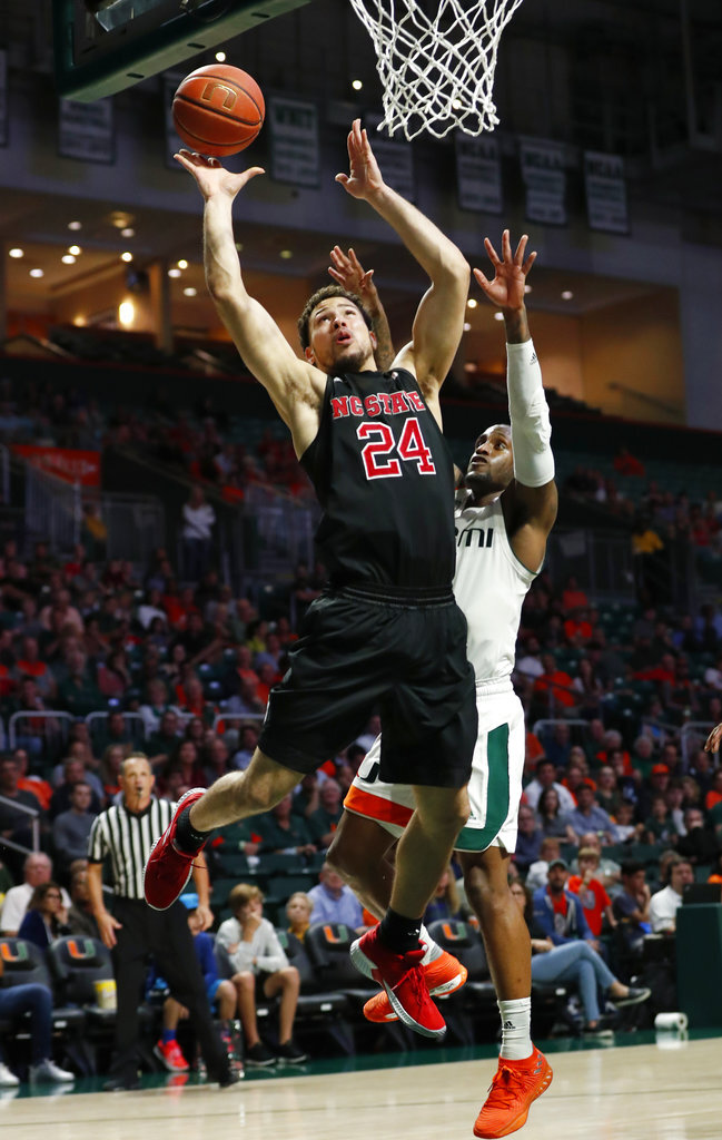 North Carolina State guard Devon Daniels (24) goes up for a shot against Miami guard Zach Johnson during the second half of an NCAA college basketball game, Thursday, Jan. 3, 2019, in Coral Gables, Fla. North Carolina State defeated Miami 87-82. (AP Photo/Wilfredo Lee)