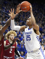 Kentucky's PJ Washington, right, shoots while defended by South Carolina's Chris Silva, left, and Hassani Gravett, center, during the first half of an NCAA college basketball game in Lexington, Ky., Tuesday, Feb. 5, 2019. (AP Photo/James Crisp)