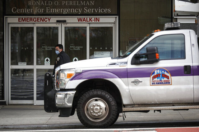 In this March 16, 2020, photo an NYPD officer wearing a protective face mask monitors the outside of the NYU Langone Hospital Emergency room entrance in New York. Brooklyn's district attorney announced Tuesday, March 17, that because of the crisis his office is declining to prosecute low-level offenses that don't jeopardize public safety. (AP Photo/John Minchillo, File)