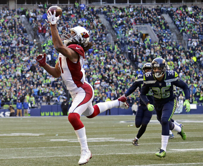 "FILE - In this Dec. 30, 2018, file photo, Arizona Cardinals' Larry Fitzgerald, left, snags a one-handed touchdown pass against the Seattle Seahawks during the first half of an NFL football game, in Seattle. Star receiver Larry Fitzgerald is returning to the Arizona Cardinals for a 16th NFL season. The Cardinals announced Wednesday, Jan. 23, 2019, that they signed the 35-year-old Fitzgerald to a one-year contract. Team president Michael Bidwell says, ""No player has meant more to this franchise or this community than Larry Fitzgerald.""(AP Photo/John Froschauer, File)"