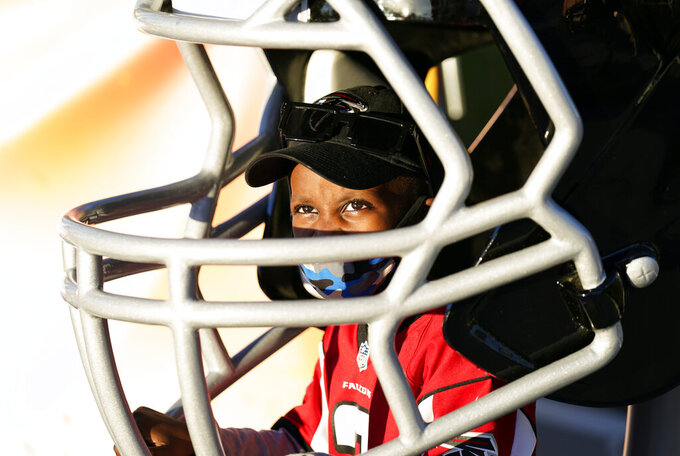 Isaiah Sheppard, 7, sits inside an oversized football helmet at the NFL Experience for Super Bowl LV Friday, Jan. 29, 2021, in Tampa, Fla. (AP Photo/David J. Phillip)