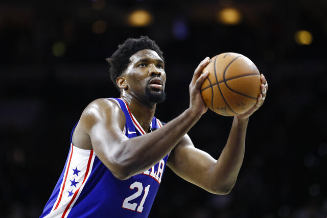FILE - In this March 11, 2020 file photo, Philadelphia 76ers' Joel Embiid plays during an NBA basketball game against the Detroit Pistons in Philadelphia. Embiid is hurting, and that's a cause for concern as the Philadelphia 76ers get set to restart their season this week. The All-Star starting center sat out Philadelphia's scrimmage against Oklahoma City on Sunday, July 26 with right calf tightness, something 76ers coach Brett Brown hopes is merely a minor blip. (AP Photo/Matt Slocum, File)