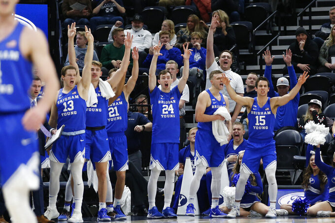 The BYU bench celebrates in the first half of an NCAA college basketball game against Utah State, Saturday, Dec. 14, 2019, in Salt Lake City. (AP Photo/Rick Bowmer)