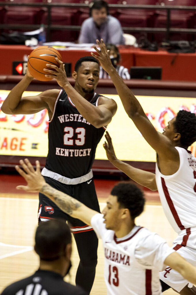 Western Kentucky center Charles Bassey (23) looks for a way inside against Alabama forward Jordan Bruner (2) during the first half of an NCAA college basketball game, Saturday, Dec. 19, 2020, in Tuscaloosa, Ala. (AP Photo/Vasha Hunt)