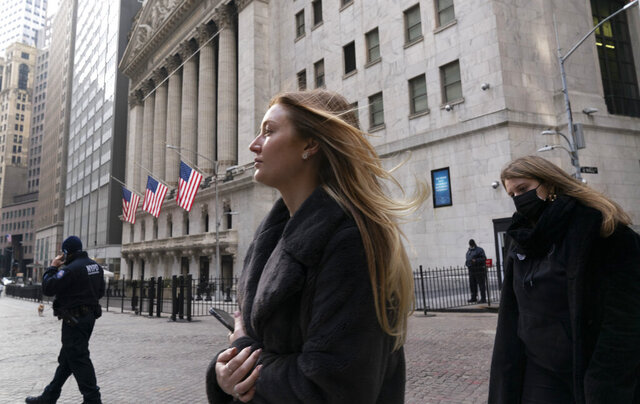 FILE - In this Wednesday, Jan. 13, 2021 file photo, people walk by the New York Stock Exchange. Stocks are climbing Tuesday, Jan. 19 recovering some of last week's losses to pull closer to their record highs. The S&P 500 was 0.6% higher in early trading and got back within 1% of its record set earlier this month. (AP Photo/Mark Lennihan, File)