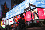 A screen displaying a messages thanking healthcare workers due to COVID-19 concerns is displayed in a sparsely populated Times Square, Friday, March 20, 2020, in New York. New York Gov. Andrew Cuomo is ordering all workers in non-essential businesses to stay home and banning gatherings statewide.