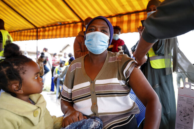 A Kenyan woman receives a dose of AstraZeneca coronavirus vaccine donated by Britain, at the Makongeni Estate in Nairobi, Kenya Saturday, Aug. 14, 2021. In late June, the international system for sharing coronavirus vaccines sent about 530,000 doses to Britain – more than double the amount sent that month to the entire continent of Africa. It was the latest example of how a system that was supposed to guarantee low and middle-income countries vaccines is failing, leaving them at the mercy of haphazard donations from rich countries. (AP Photo/Brian Inganga)