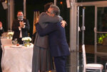 In this video grab captured on Sept. 20, 2020, courtesy of the Academy of Television Arts & Sciences and ABC Entertainment, Dan Levy, left, hugs his father Eugene Levy, winner of the award for outstanding lead actor in a comedy series for