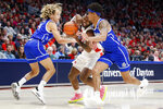Dayton's Trey Landers, center, drives against Drake's Anthony Murphy, right, Noah Thomas, left, during the first half of an NCAA college basketball game, Saturday, Dec. 14, 2019, in Dayton, Ohio. (AP Photo/John Minchillo)
