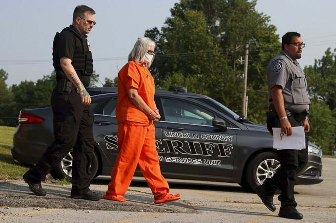 """Pamela Hupp is escorted from the Lincoln County Justice Center to the detention center following a hearing, Tuesday, July 27, 2021, in Troy, Mo. Hupp, already serving a life sentence for murder, pleaded not guilty Tuesday in the stabbing death of her friend a decade ago. Hupp is charged with first-degree murder and armed criminal action in the death of Elizabeth """"Betsy"""" Faria, in 2011.  (Christian Gooden/St. Louis Post-Dispatch via AP)"""
