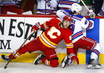 New York Rangers' Brendan Lemieux, right, is checked by Calgary Flames' Sam Bennett  during the third period of an NHL hockey game in Calgary, Alberta, Friday, March 15, 2019. (Jeff McIntosh/The Canadian Press via AP)