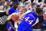 Kansas forward Mitch Lightfoot (44) strips the ball from Texas Tech's Mac McClung (0) during the first half of an NCAA college basketball game in Lubbock, Texas, Thursday, Dec. 17, 2020. (AP Photo/Justin Rex)