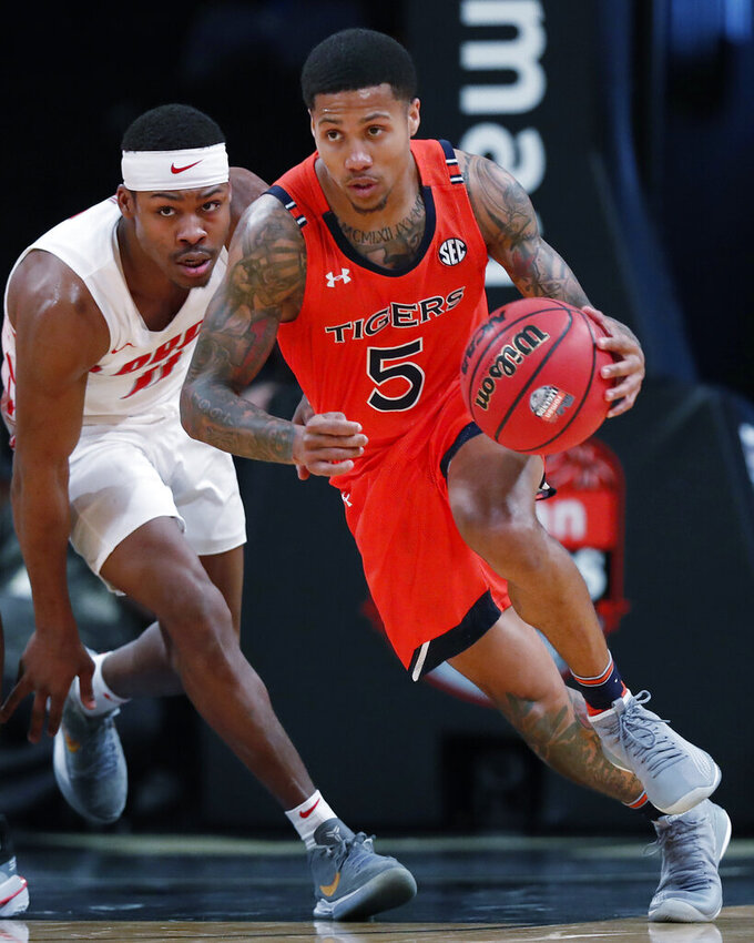 Auburn guard J'Von McCormick (5) drives the ball down court with New Mexico guard JJ Caldwell (11) in pursuit during the second half of an NCAA college basketball game in the Legends Classic, Monday, Nov. 25, 2019, in New York. Auburn defeated New Mexico 84-59. (AP Photo/Kathy Willens)