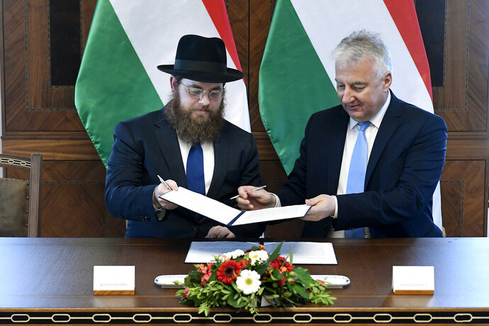 Deputy prime minister in charge of Hungarian communities abroad, church policy and national and ethnic minorities, Zsolt Semjen, right, and Chief Rabbi of the Unified Israelite Congregation of Hungary (EMIH) Slomo Koves sign a comprehensive agreement at the Castle District premises of the Prime Minister's Office, in Budapest, Hungary, Monday, Nov. 18, 2019. By signing the agreement, the Hungarian state acknowledges the historical traditions of the Jewish community and