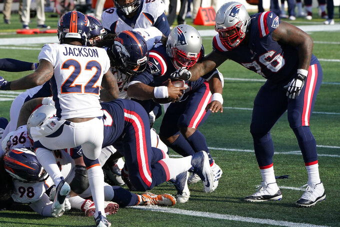 New England Patriots quarterback Cam Newton, center, bulls his way to the goal line and a touchdown in the second half of an NFL football game against the Denver Broncos, Sunday, Oct. 18, 2020, in Foxborough, Mass. (AP Photo/Steven Senne)