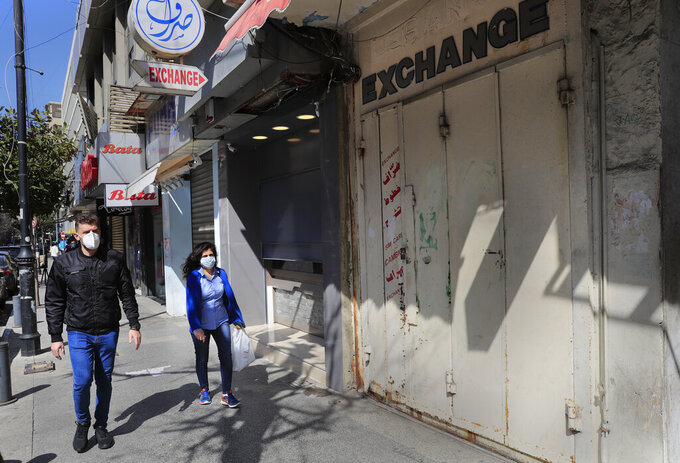 People pass next of an exchange shop which seen close amid a crackdown on some exchange shops by authorities around the country that the blame for inciting the crisis, at Beirut's commercial Hamra Street, in Beirut, Lebanon, Tuesday, March 16, 2021.  More than half the population now lives in poverty, while an intractable political crisis heralds further collapse and Lebanese are gripped by fear for the future. (AP Photo/Hussein Malla)