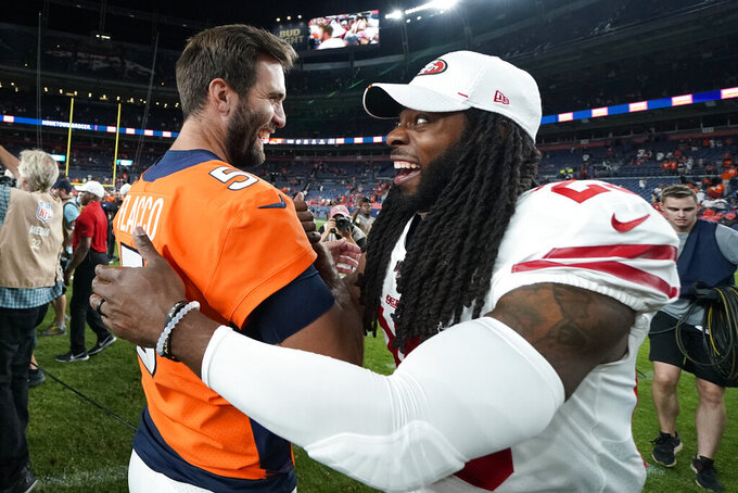 Denver Broncos quarterback Joe Flacco (5) talks with San Francisco 49ers cornerback Richard Sherman (25) after an NFL preseason football game, Monday, Aug. 19, 2019, in Denver. The 49ers won 24-15. (AP Photo/Jack Dempsey)