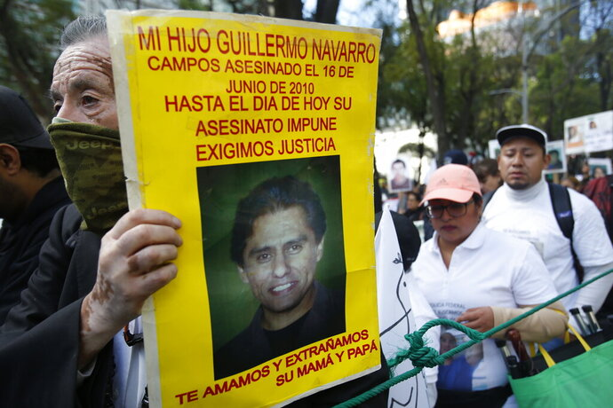A demonstrator carries a poster with the photo of his murdered son during a march against violence called